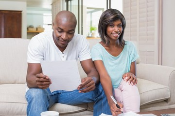 Confident couple calculating bills on the couch