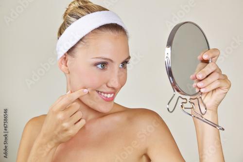 79ed8684f564 Frau schaut im Spiegel nach Falten