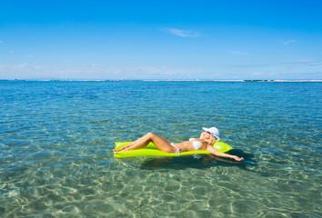 Woman floating on raft in tropical ocean