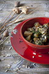 roasted japanese turnips with leaves and seeds on red bowl