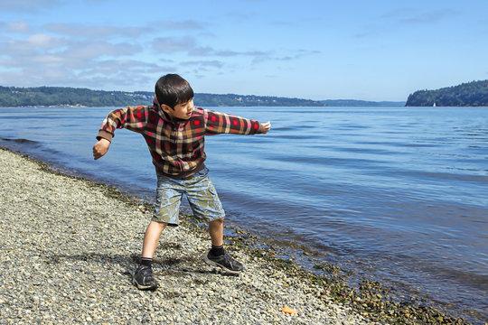 Boy skips a rock in the water.