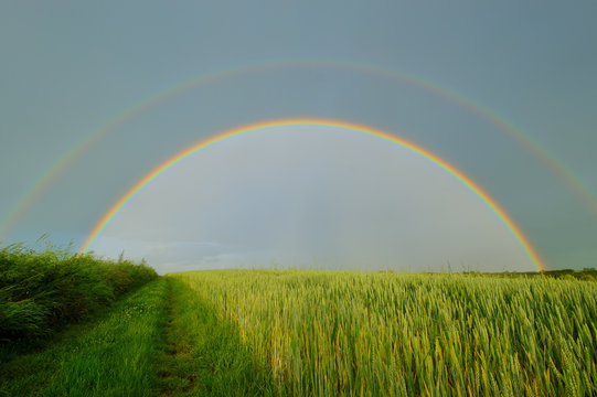 Double full rainbow over country road.