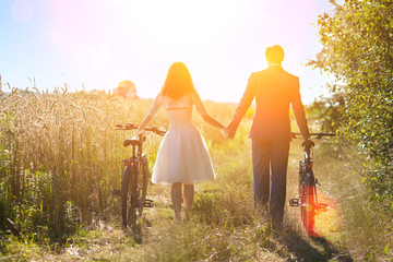 Young happy bride and groom carry bikes in the field