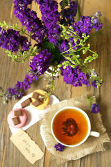 Cup of fresh herbal tea on wooden table