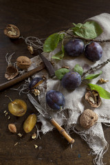 Prunes with leafs and walnuts on rustic background
