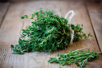 bunch of fresh thyme on a wooden background