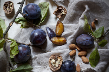 Prunes with leafs, walnuts, almonds on rustic background