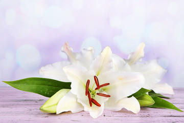 Beautiful lily on table on bright background