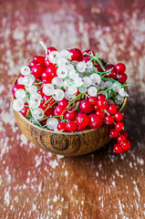 Red and white currants on wooden background
