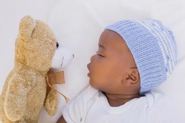 Adorable baby boy sleeping peacefully with teddy