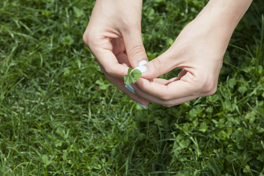woman holding clover with 4 leaves