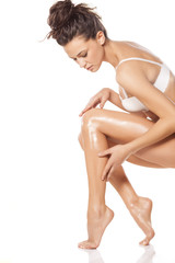beautiful young woman apply lotion on her legs
