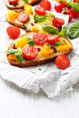 Tasty bruschetta with tomatoes, on table
