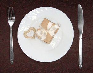 Gift box with white heart on plate