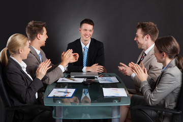 Business People Applauding For Male Colleague After Presentation