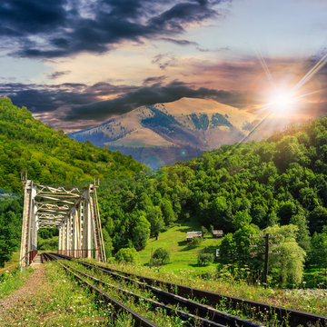 old railroad passes in mountain village at sunset
