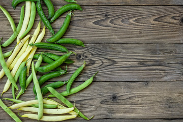 Green peas and green beans on wooden background