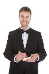 Mid Adult Waiter Writing On Notepad