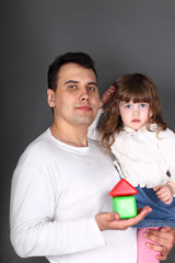 Father holding his daughter and a house from cubes