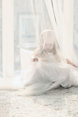 Pretty little blonde girl sits near big window and hides
