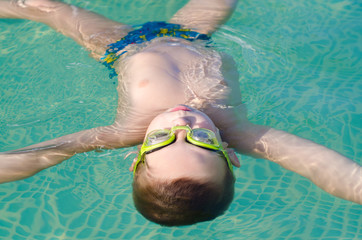 Little boy floating on the water surface of the swimming pool
