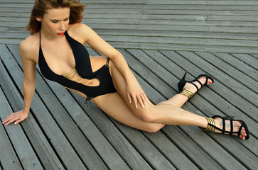 Fashion model posing on boardwalk wearing black swimsuit