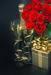 red roses, golden gift box and and champagne on black background