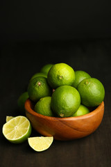 Fresh juicy limes in wooden bowl, on dark background