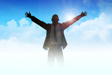 Silhouette of a man with open arms among the clouds