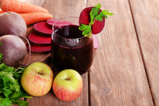 Glass of fresh beet juice and vegetables on wooden background