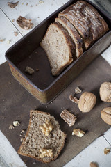 homemade wholemeal sliced bread on vintage box with walnuts