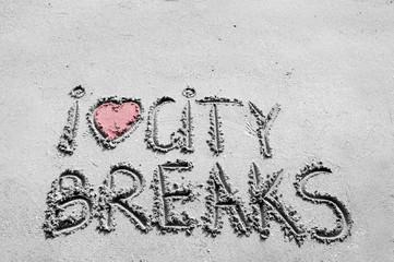 I Love City Breaks message written on sand, color filter applied