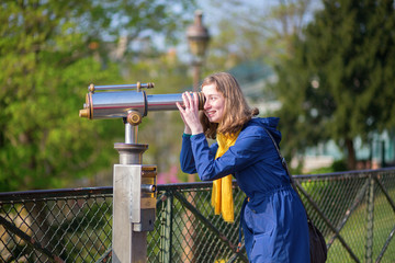 Girl using telescope for sightseeing in Paris