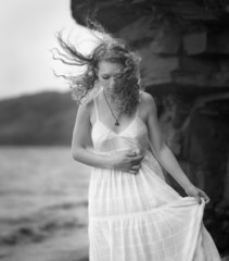Young woman goes along the coast. Black and white image.