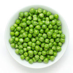 Fresh garden peas in a ceramic dish shot from above.