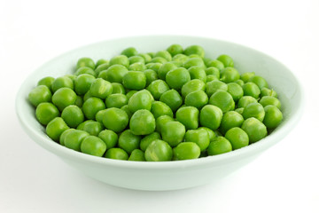 Detail of fresh garden peas in a white ceramic bowl.