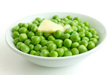 Fresh garden peas in a white bowl. Melting butter.
