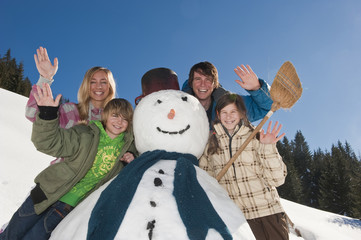 Familie, die durch Schneemann, winken , Portrait