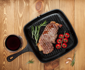Sirloin steak with rosemary and cherry tomatoes on frying pan