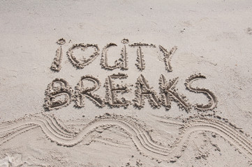 I Love City Breaks message written on sand, vacation concept