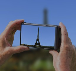 woman taking picture of eiffel tower on holiday