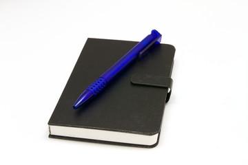 Schwarzes Notizbuch mit blauem Kugelschreiber