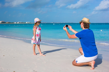 Young father making photo on phone of little girl at beach
