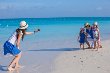 Young mother making photo on phone of her family at the beach