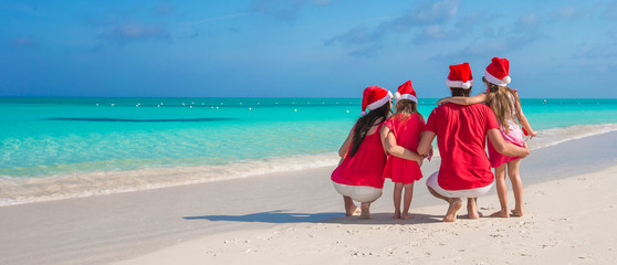 Two parents and kids in Santa Hat on white beach
