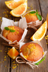 Tasty cupcakes with orange on table close-up