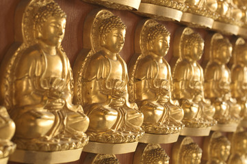 Shallow depth of field of numerous golden Buddha image