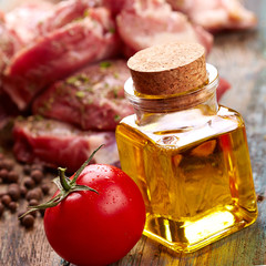 Oil bottle with meat steak over wooden background