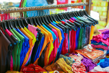 A rack of colorful shirts hanged for sale at a fair