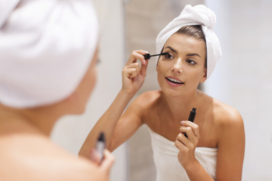 Beautiful woman using mascara in bathroom